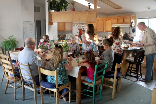 Members of the Greenwave intentional community, as well as three guests who were visiting a family member, sit down to eat in the community's kitchen, where they eat once a week together. Photo by Veronica Weber.
