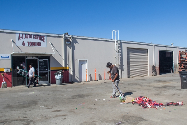 jos ramirez right sweeps up streamers and party decorations left behind from a halloween party at the rear of a 1 auto service and towing in east palo